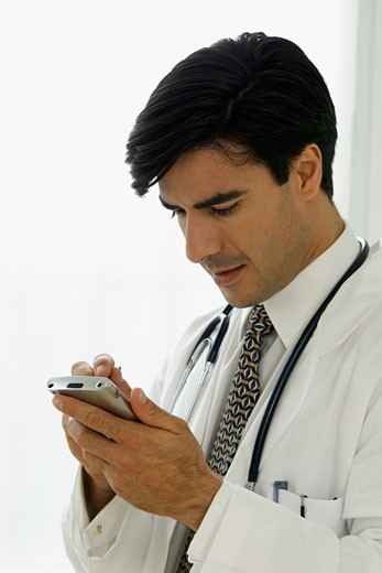 Male doctor using PDA : Stock Photo