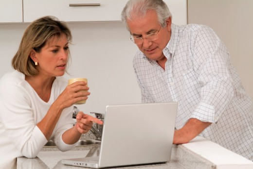 Man and woman in kitchen using laptop, close-up : Stock Photo