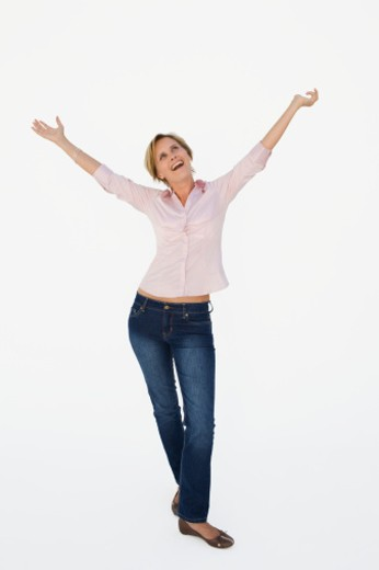 Mid adult woman with raised hands, looking up, smiling : Stock Photo