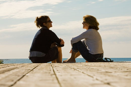 Two woman sitting on pier by ocean : Stock Photo