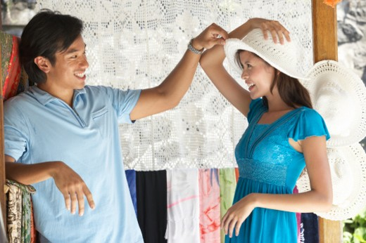 Stock Photo: 1598R-242155 Young couple in fabric shop, woman trying on hat