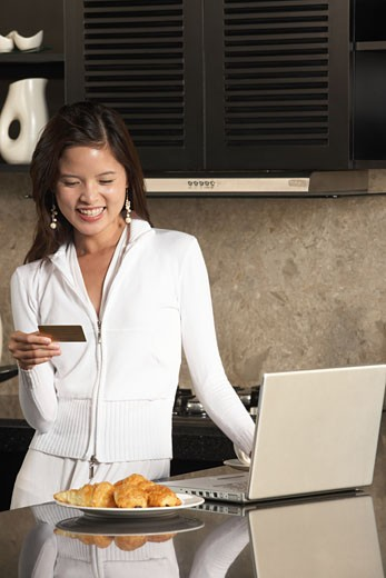 Young woman using laptop and credit card in kitchen : Stock Photo