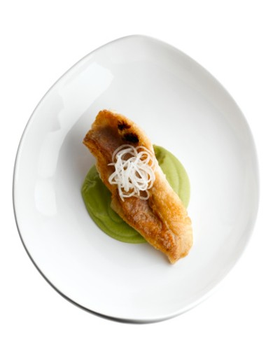 Rouget on pea puree served on white plate : Stock Photo