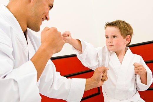 Boy (4-5 years) performing karate punches with man : Stock Photo