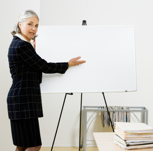 Stock Photo: 1598R-242626 Senior business woman presenting chart in office meeting