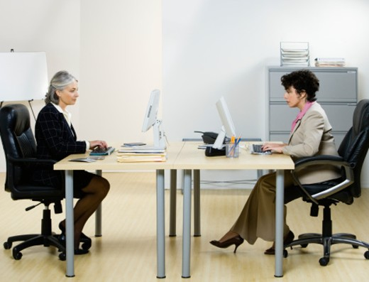 Stock Photo: 1598R-242638 Two business women using computers at desk in office