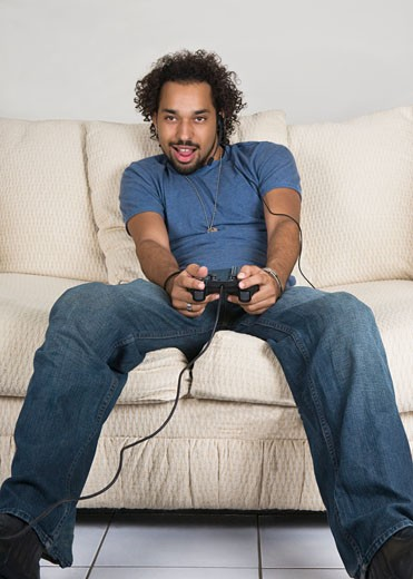 Young man sitting on sofa and playing video game : Stock Photo