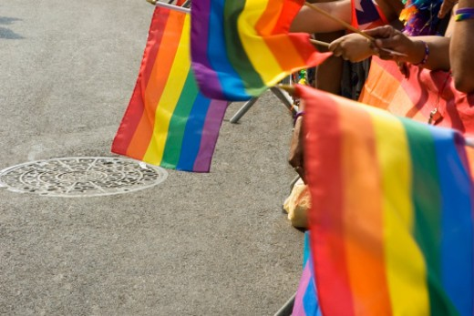 Rows of hands holding gay pride, rainbow-colored flags, close-up : Stock Photo