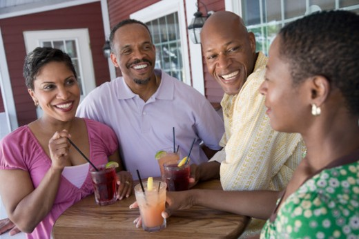 Mid adult couple and a mature couple smiling at a table : Stock Photo