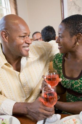 Close-up of a mid adult couple holding glasses of red wine : Stock Photo