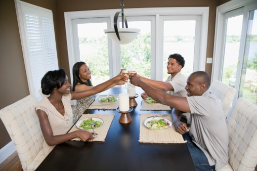 Two young couples toasting with wine glasses at the dining table : Stock Photo