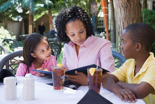 Mid adult woman with his son and daughter reading a menu at the breakfast table : Stock Photo