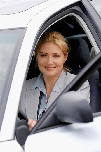 Mid adult business woman sitting in a car, smiling : Stock Photo