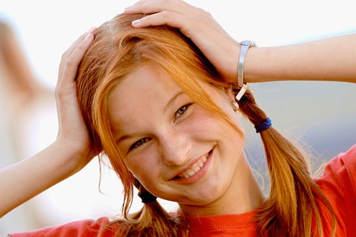Girl smiling with her hands on her head : Stock Photo