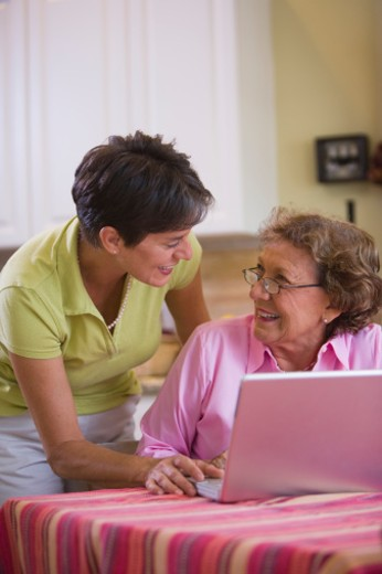 Mother and adult daughter using laptop in room : Stock Photo