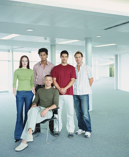 Group of colleagues in empty office, mature man sitting, portrait : Stock Photo