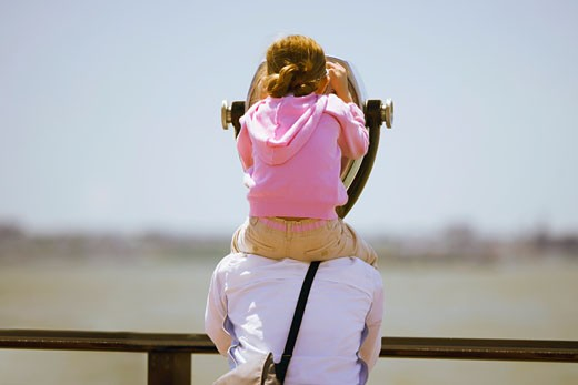 Girl sitting on parent's shoulders to look through tourist sight-seeing camera : Stock Photo