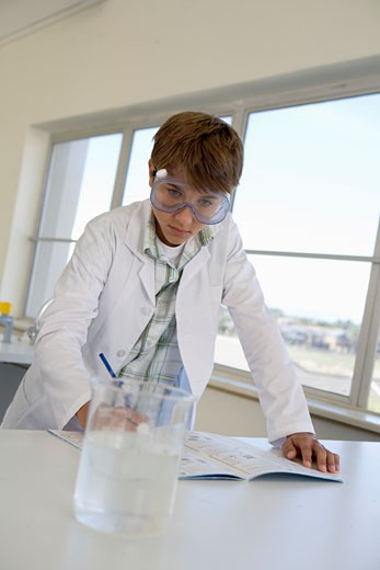 Boy (12-13) wearing safety goggles, doing chemistry experiment in class, writing notes : Stock Photo