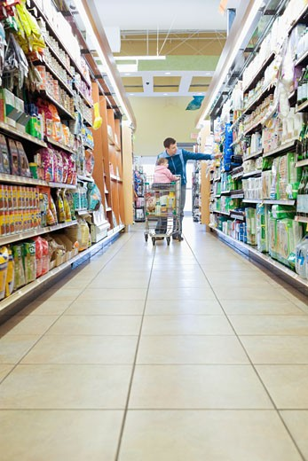 Man with daughter (18-21 months) in trolley in supermarket aisle, full length : Stock Photo
