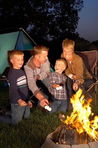 Stock Photo: 1598R-247298 Family with two sons (4-6 years) roasting marshmallows around campfire