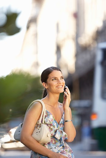 Young woman using mobile phone, outdoors, smiling : Stock Photo