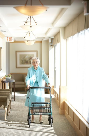 Stock Photo: 1598R-248935 Senior woman walking down hallway with walker
