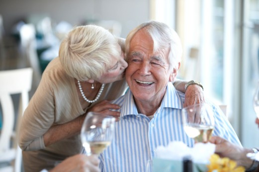 Senior couple in restaurant, woman kissing man on cheek : Stock Photo