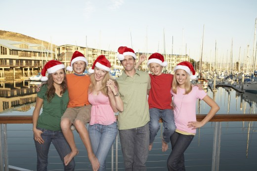 Stock Photo: 1598R-249187 Portrait of family with three kids (12-17) on dock, all wearing santa hats