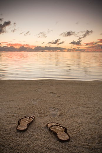 French Polynesia, Bora Bora, Sandals and foot prints in sand on beach at dusk : Stock Photo