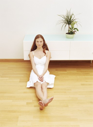 Stock Photo: 1598R-249840 Young woman sitting on floor leaning against sideboard, ankles crossed