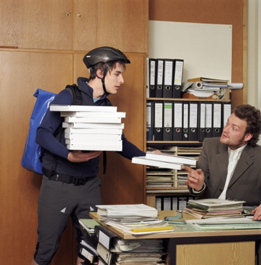 Stock Photo: 1598R-249862 Delivery man handing parcels to businessman