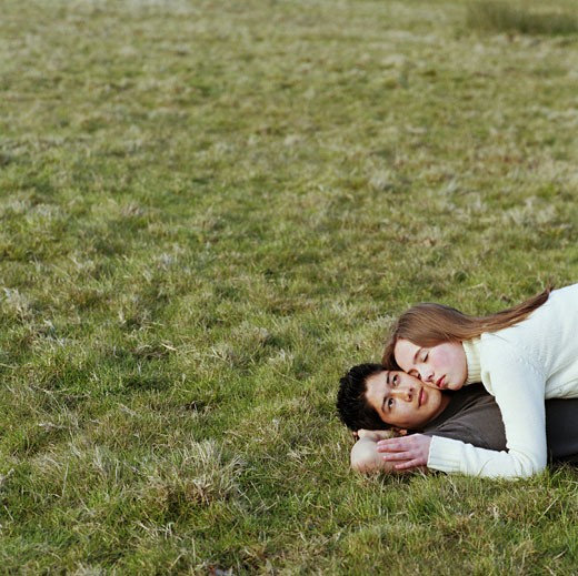 Stock Photo: 1598R-250003 Teenage couple (15-17) lying on grass
