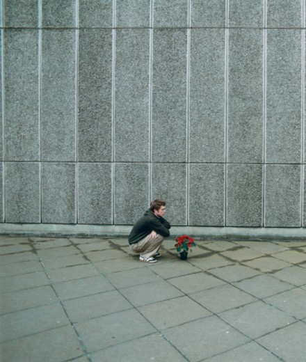 Stock Photo: 1598R-250310 Man Crouching By Plant