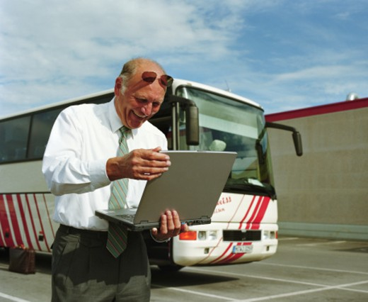 Stock Photo: 1598R-25559 Businessman looking at laptop, smiling, bus in background