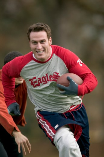 Man running with football, other man reaching to tackle : Stock Photo