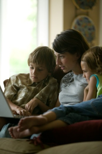 Mother and children (4-5) using laptop sitting on sofa in living room : Stock Photo