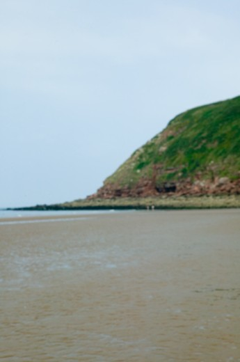 Headland by sea at low tide : Stock Photo