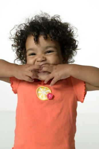 Stock Photo: 1598R-259561 Young girl (4-5) with frizzy hair posing indoors with hands in mouth, close-up