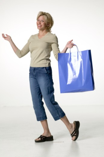 Woman carrying paper bag in studio, portrait : Stock Photo