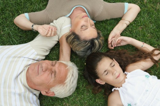 Grandparents and granddaughter (8-10) holding hands lying on grass : Stock Photo