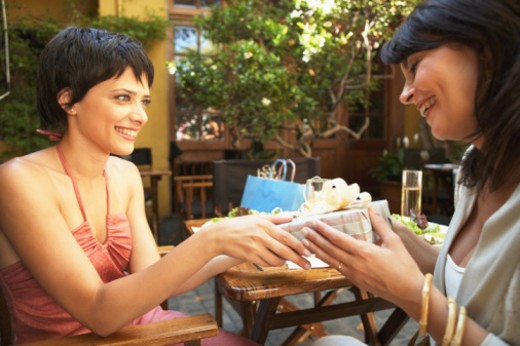 Two young women exchanging gift in restaurant, smiling : Stock Photo