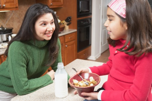 Mother talking to her daughter in the kitchen : Stock Photo