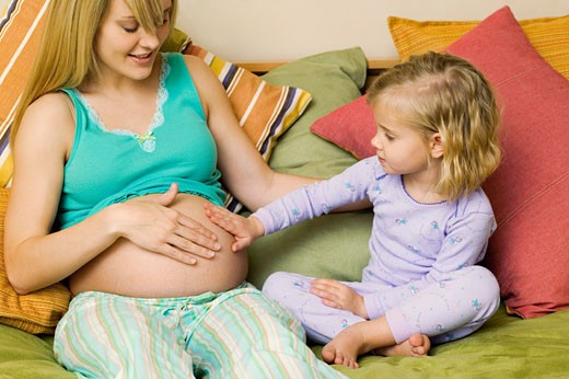 Girl (4-5) sitting on bed touching belly of pregnant mother : Stock Photo