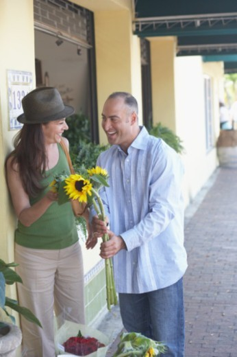 Stock Photo: 1598R-262717 Mid adult man giving sunflowers to a mature woman