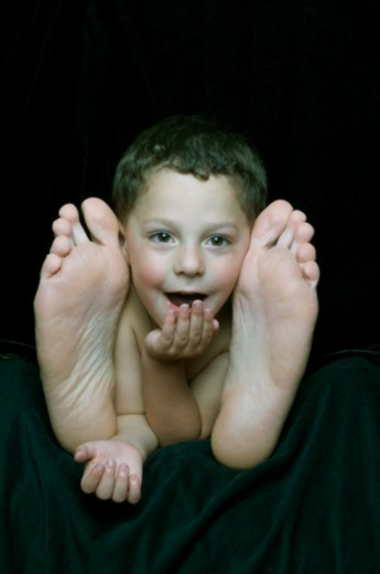 Stock Photo: 1598R-262981 Boy (2-4) lying between father's feet, resting chin on hand, smiling