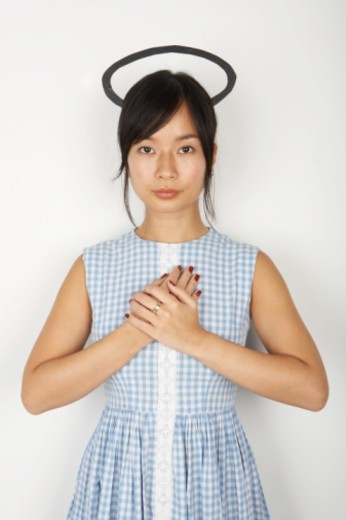 Woman with hands together on chest and halo above her head, portrait : Stock Photo