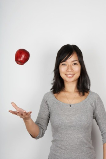Stock Photo: 1598R-263446 Woman throwing up apple smiling, portrait