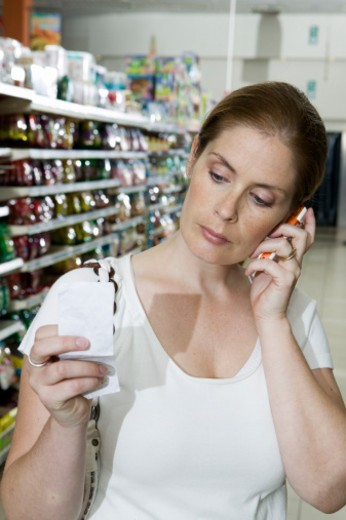 Woman using mobile telephone in supermarket, looking at shopping list : Stock Photo