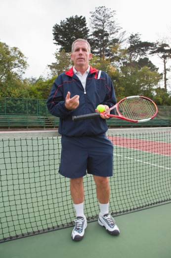 Mature man standing on tennis court, portrait : Stock Photo