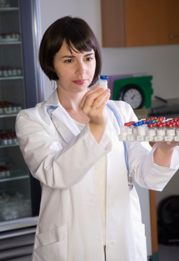 Young female lab technician holding tray of vials in laboratory : Stock Photo